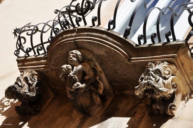 Mascheroni in un balcone di Palazzo La Rocca a Ragusa Ibla