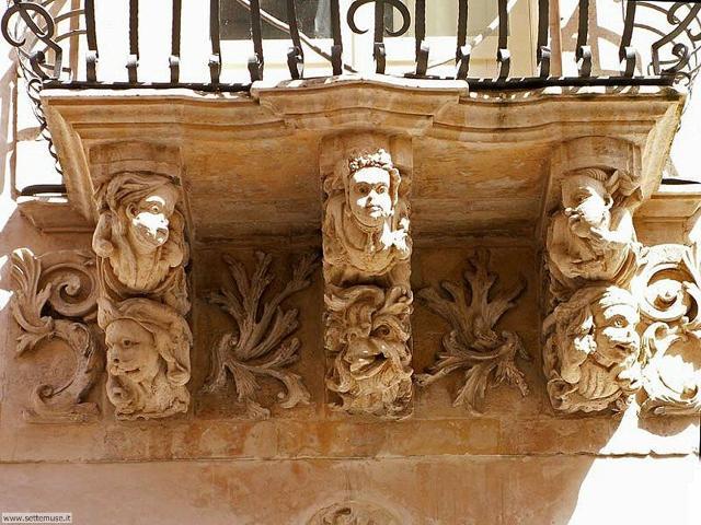 Tipici mascheroni in un balcone lungo Corso Italia a Ragusa Ibla