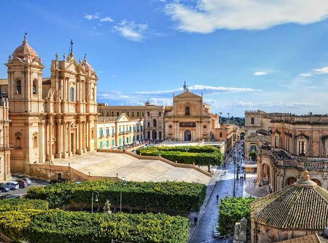 Veduta di Noto. A sinistra il Duomo (Basilica Minore di San Nicolò), in fondo il Monastero di San Salvatore; sulla destra Palazzo Ducezio, sede del Municipio