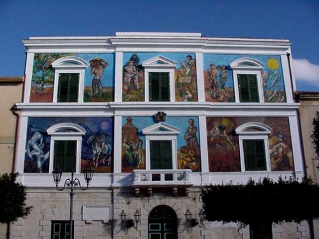La facciata del Palazzo Municipale di Campobello di Licata, dipinta da Silvio Benedetto con murales dedicati alle tradizioni popolari