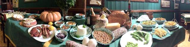 Una tavolata ricca di pietanze nell'Osteria da Salvatore a Petralia Soprana