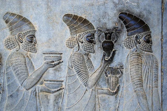 """Particolare di un rilievo sulle scale orientali dell'Apadana a Persepoli che raffigura ambasciatori di una nazione soggetta dell'impero persiano mentre portano il loro famoso vino alla presenza del """"Re dei Re""""."""
