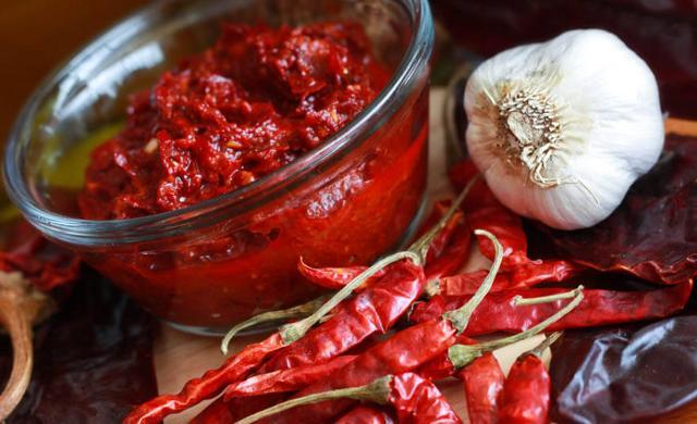 La harissa è un densa salsa preparata con peperone rosso non piccante, peperoncino piccante, olio di oliva e aromatizzato con cumino, aglio, coriandolo e menta