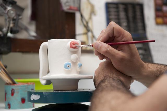 Lorenzo Camiolo nella fase di pittura del suo lavoro da ceramista