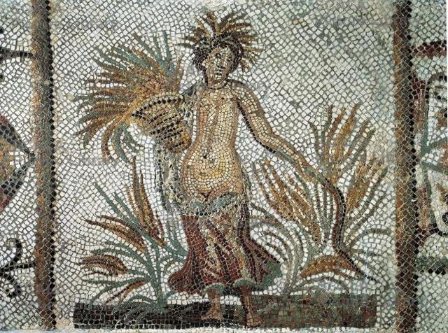 La Dea Cerere acconciata con una corona di spighe in piedi in un campo di grano. Il mosaico è conservato al Museo del Bardo di Tunisi.