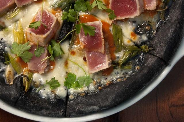 Sempre più persone prediligono le pizze ad impasto speciale. Nella foto una pizza nera preparata con un impasto al carbone vegetale e condita con tocchetti di tonno appena scottato