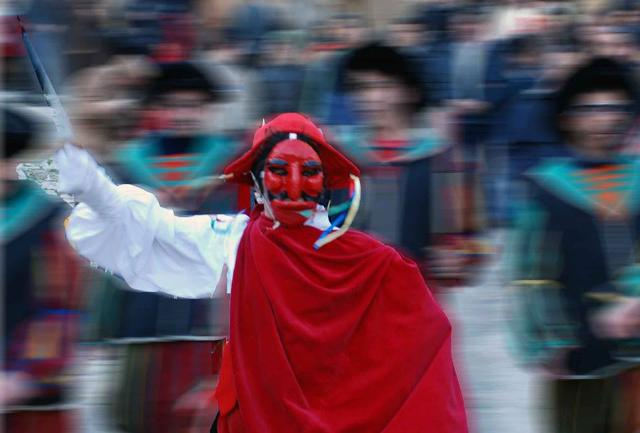 Il Mastro di Campo indossa una maschera di cera rossa con il naso adunco ed il labbro inferiore prominente, una camicia bianca piena di nastri colorati, pantaloni e mantello rosso.