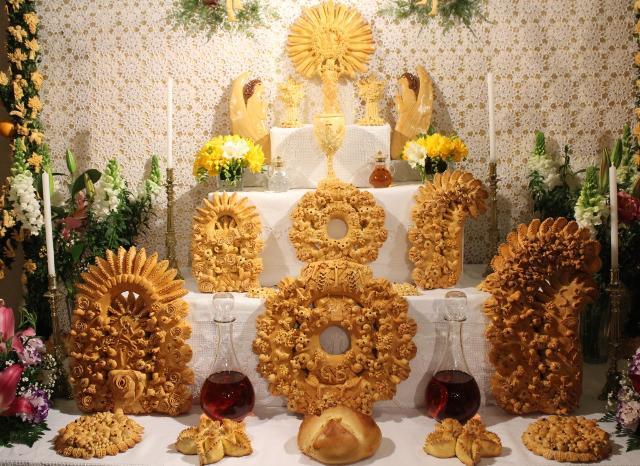 Al centro, addossato ad una parete interamente rivestita con un drappo bianco, si prepara un piccolo altare con cinque ripiani degradanti...