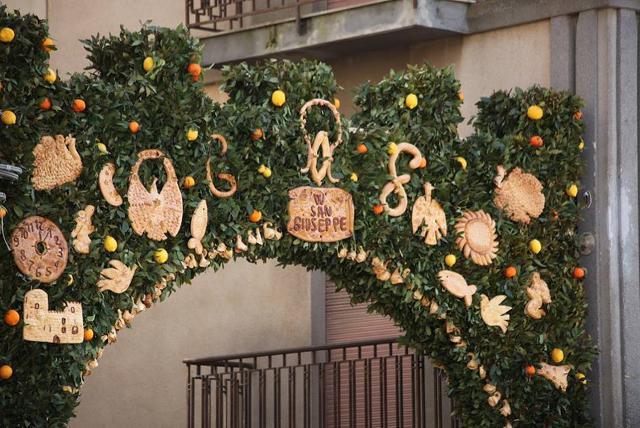 Un ramo di alloro intrecciato all'angolo della via o alla porta spalancata della casa, come una segnaletica culturale, richiama i visitatori devoti...